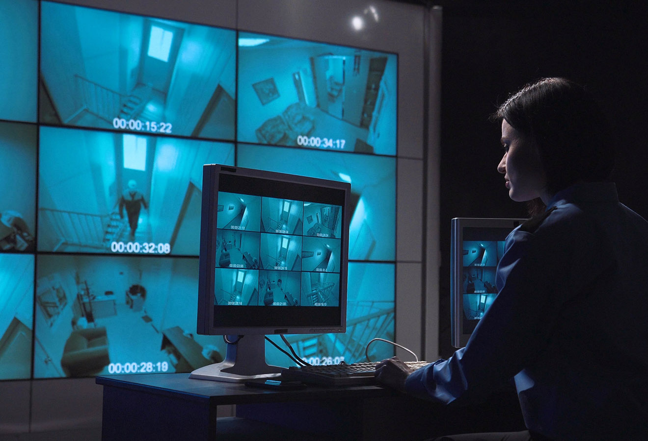 Single female security person monitoring closed circuit surveillance from multiple cameras in various rooms of a building informs on the radio to check the person who moves inside the room.